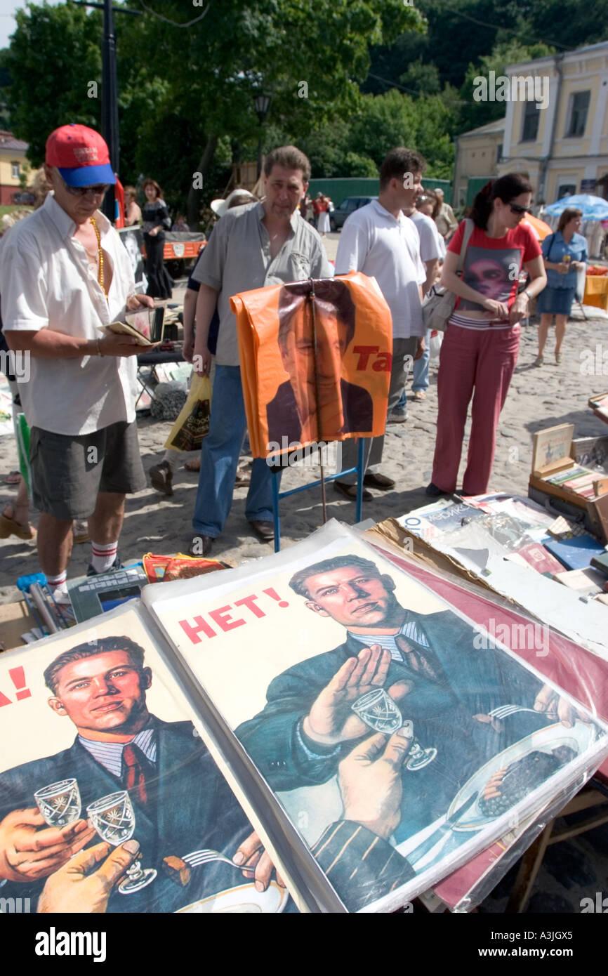 People looking at soviet posters on racks outside shop in Kiev, Ukraine 2005 - Stock Image