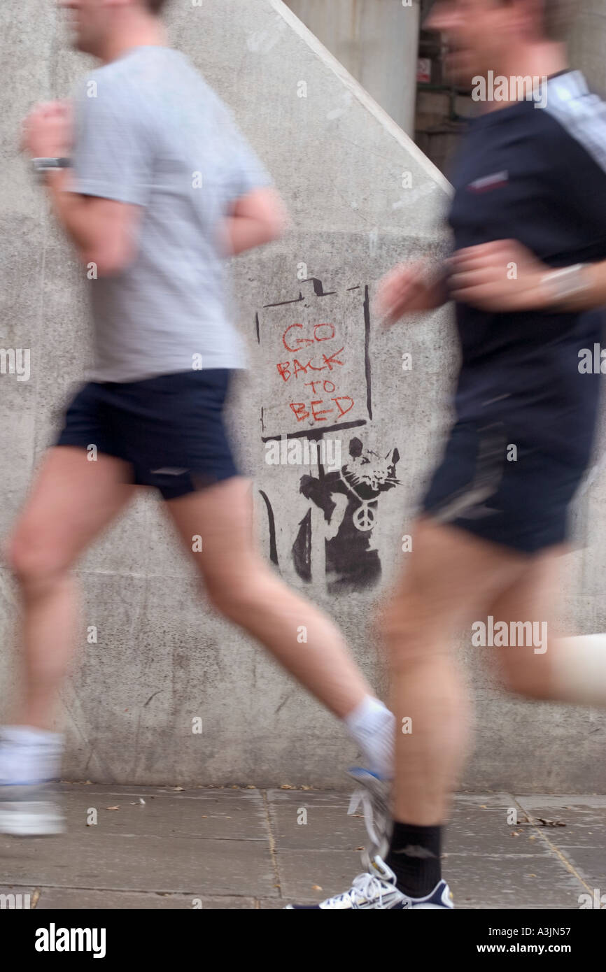 Joggers running past Banksy stencil graffiti of rat holding Go Back To Bed sign. Thames Embankment, London, England - Stock Image