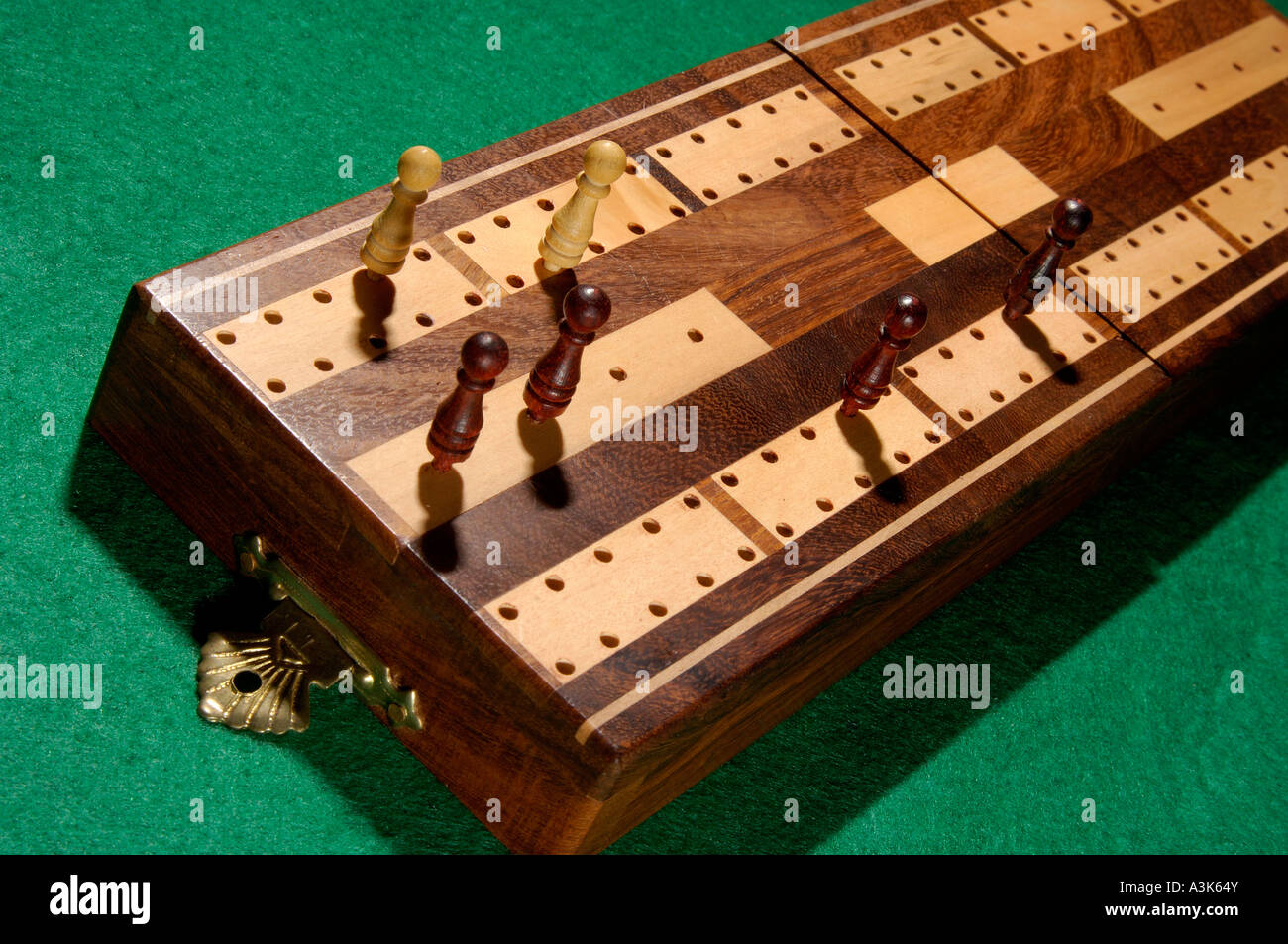 Traditional Wooden Cribbage Board With Wooden Shaped Pegs Standing On Green  Baize Card Table
