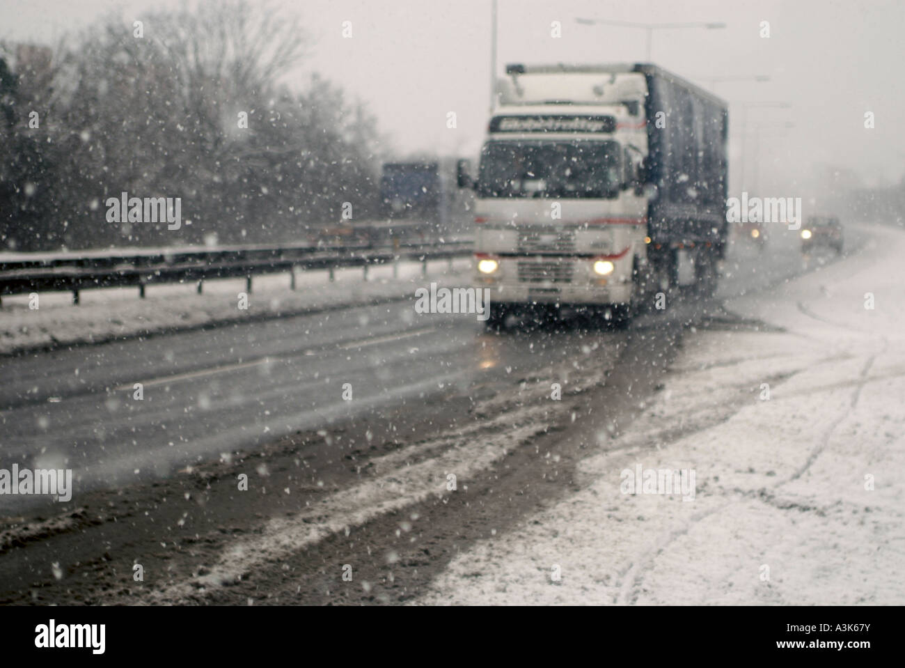 An articulated lorry drives through snow and along a snow covered arterial road. 2018122 235120 23151811 - Stock Image