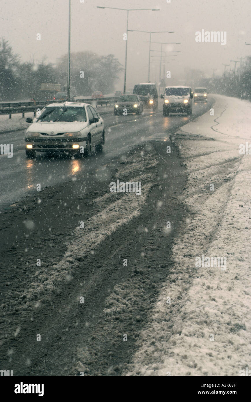 Cars drive along in freezing snow with ice and snow on an arterial road. 2018122 235120 - Stock Image