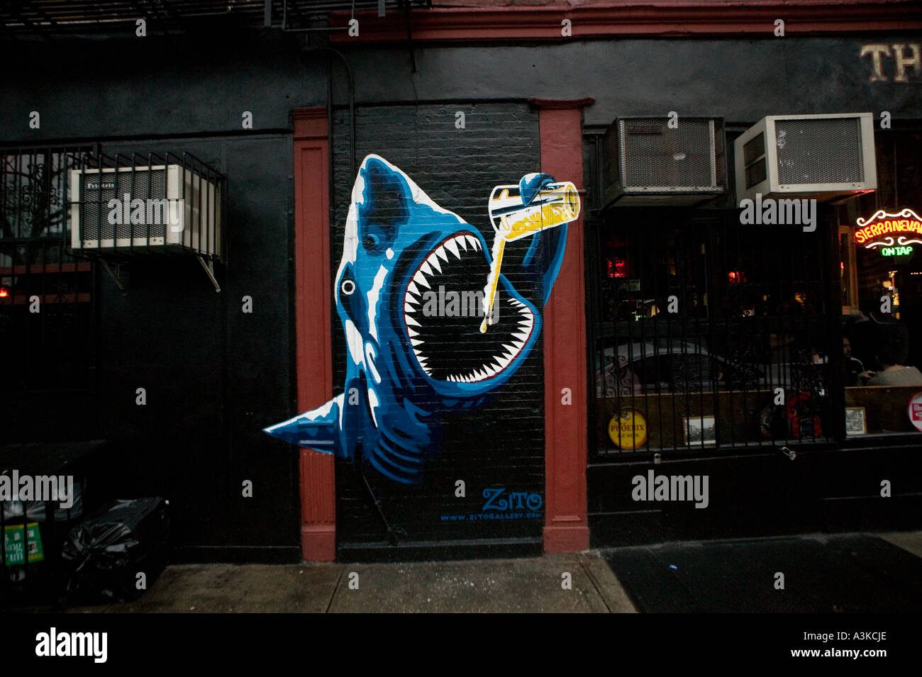 View of a beer drinking shark mural on the wall of the Spring Lounge bar on Spring Street in NoLIta New York - Stock Image