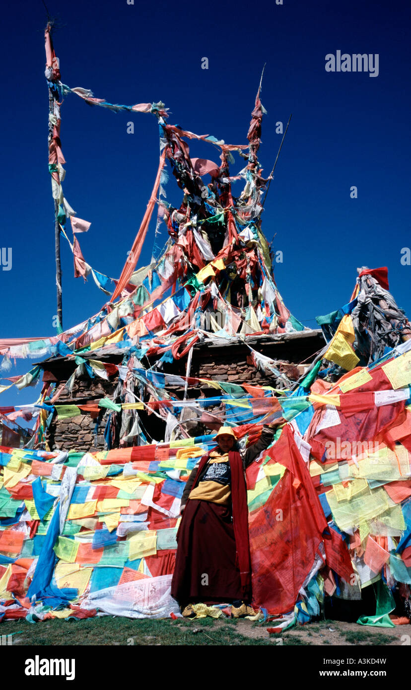 Young Tibetan friar in front of a collection of prayer flags at Chöde Gompa monastery in Litang. - Stock Image