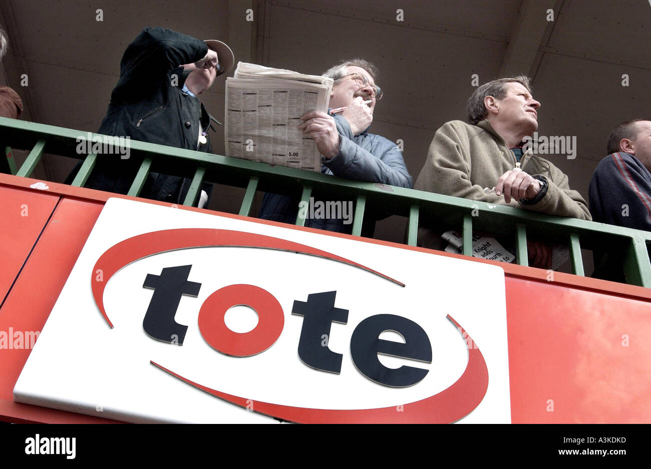 A group of punters with the racing papers sizing up form above a tote office at Lingfield Park races - Stock Image