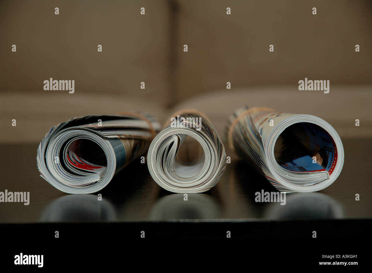 Rolled up magazines over coffee table Stock Photo