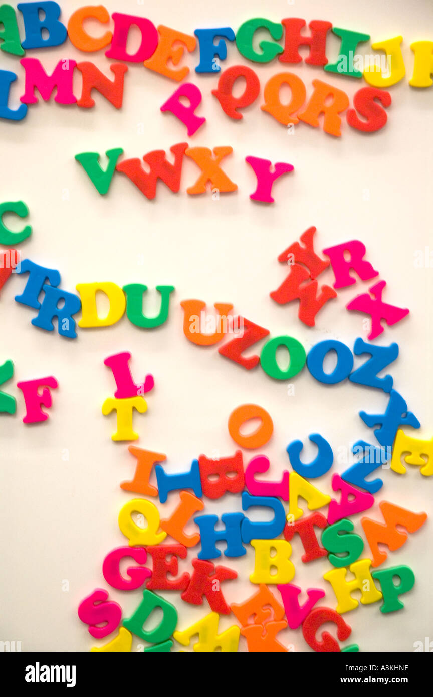 A jumble of colorful magnetic alphabet letters on a white