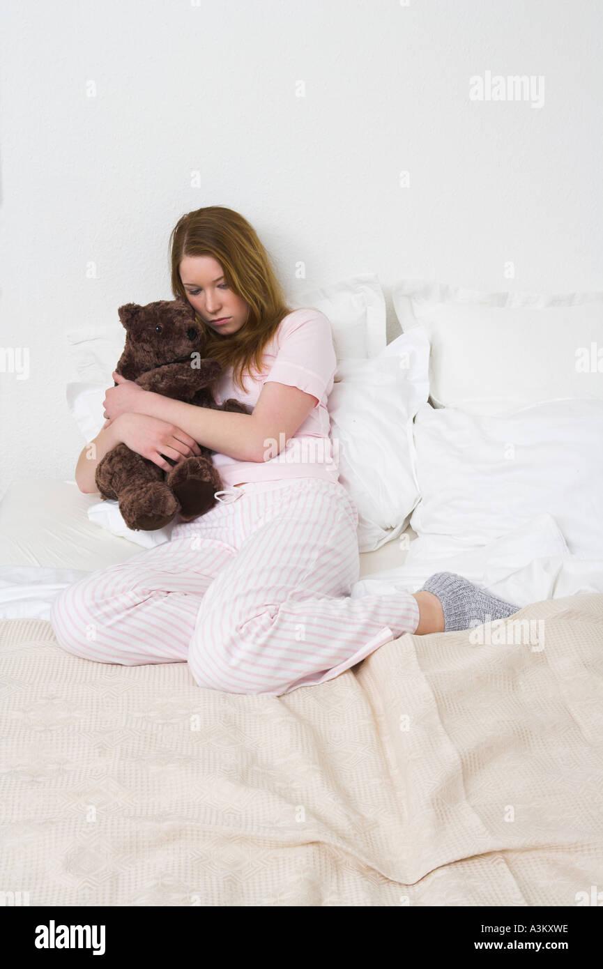 sad teenager sitting on bed and hugging teddy bear - Stock Image