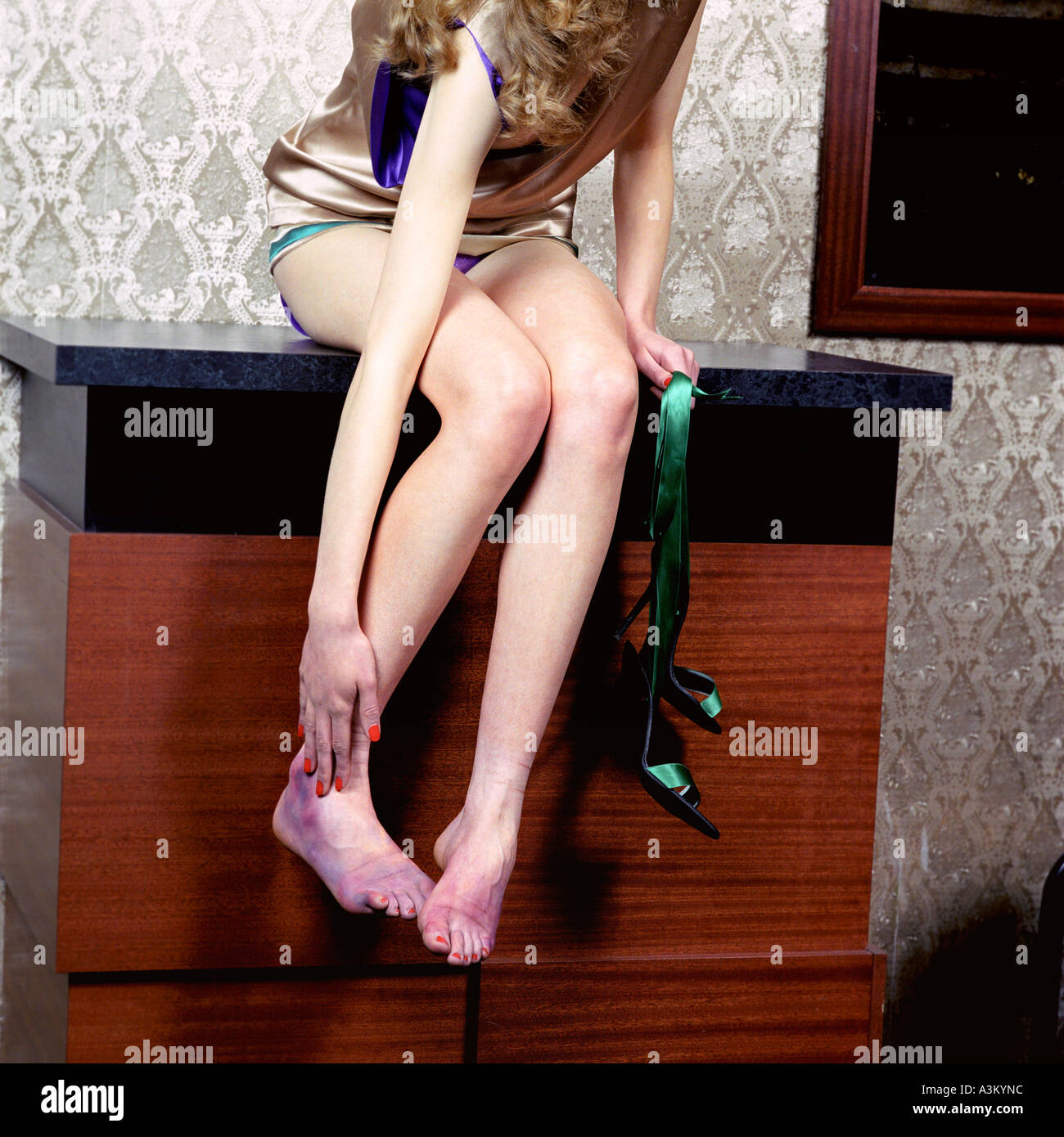 young woman sitting on chest of drawers rubbing her aching feet Stock Photo