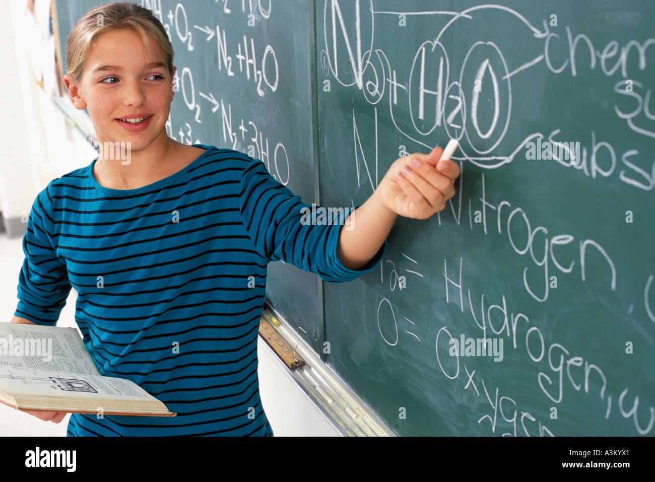 Female Caucasian student explaining elemental symbol on chalkboard - Stock Image