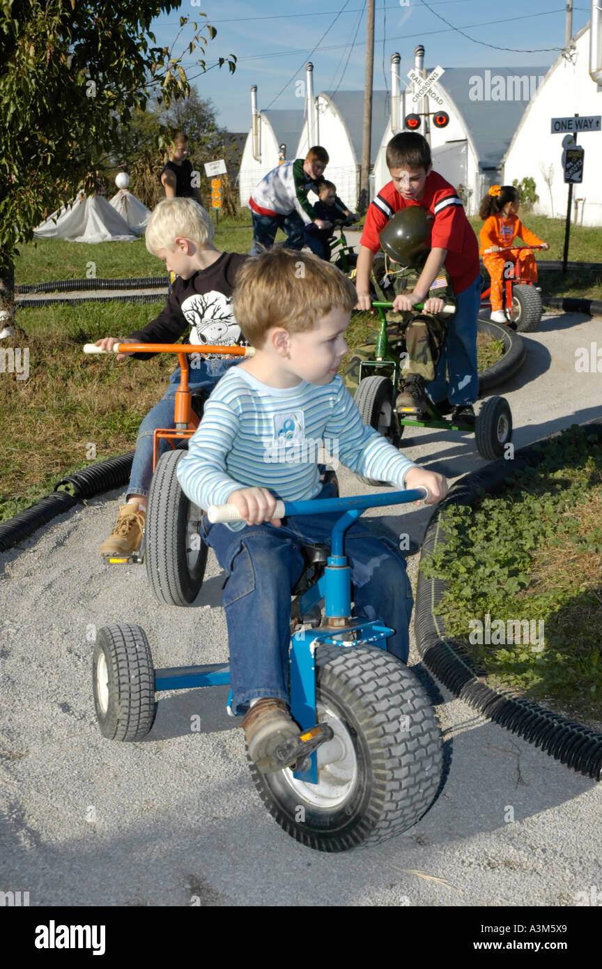 Young children having fun on a tricycle riding track - Stock Image