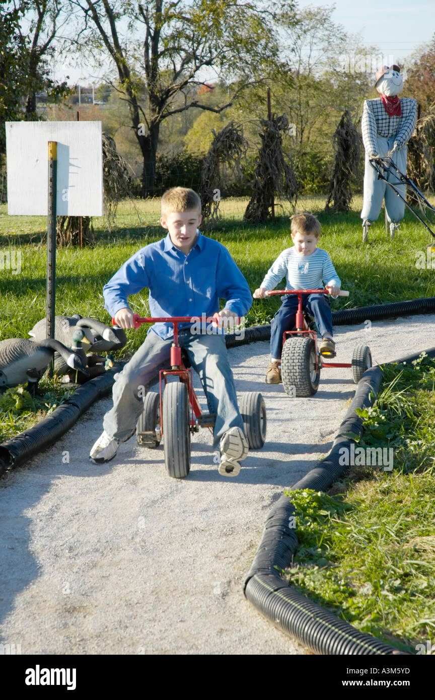 Children having fun on a tricycle riding track - Stock Image