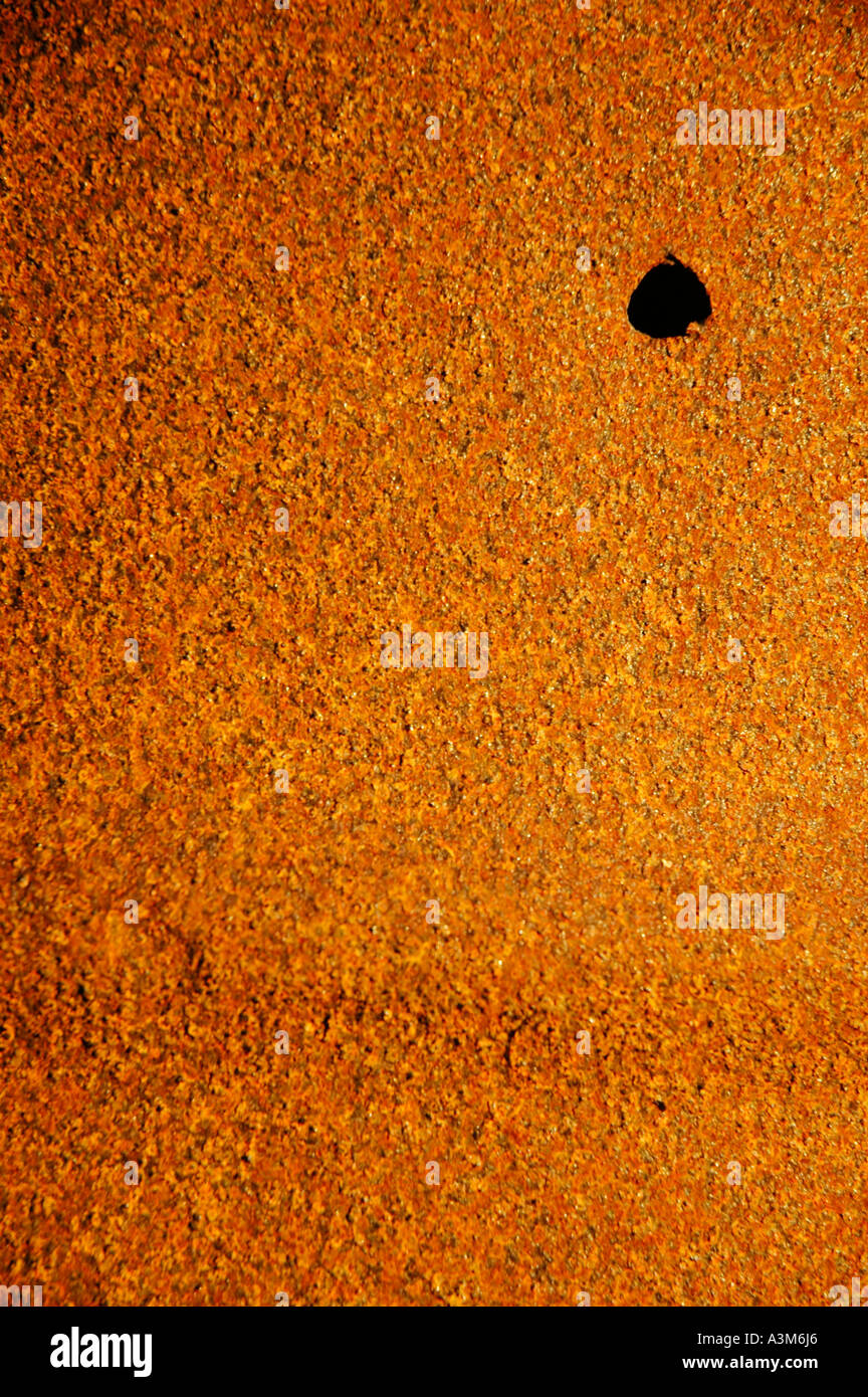 Red rust covered metal barrel with large bullet hole in upper right corner - Stock Image