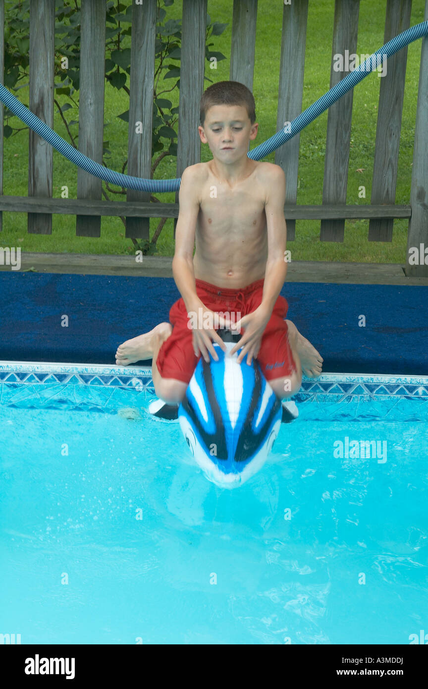 9ed87b4e5d 1 one young 8 9 eight nine year old boy enjoys swimming pool inflatable  dolphin toy