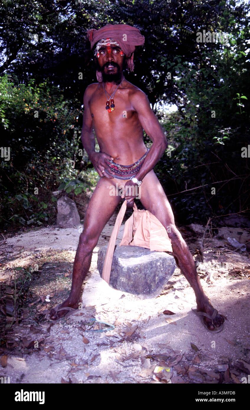 Lifting huge rock with penis. Kumbh Mela. Hardwar. Sadhus in India. Stock Photo