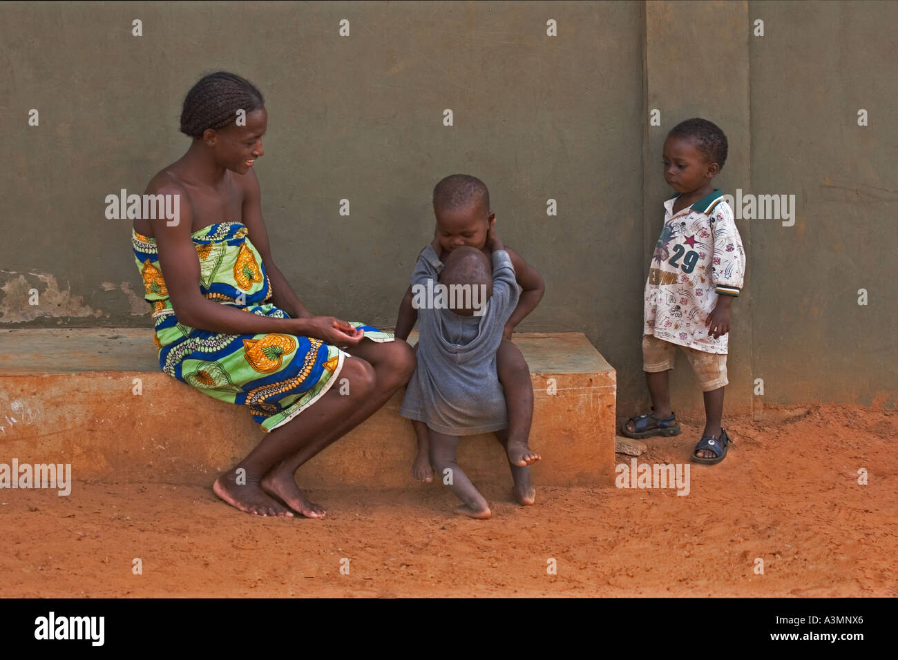 Happy African mother from Ghana and baby toddler hugging slightly older brother with another brother looking on - Stock Image