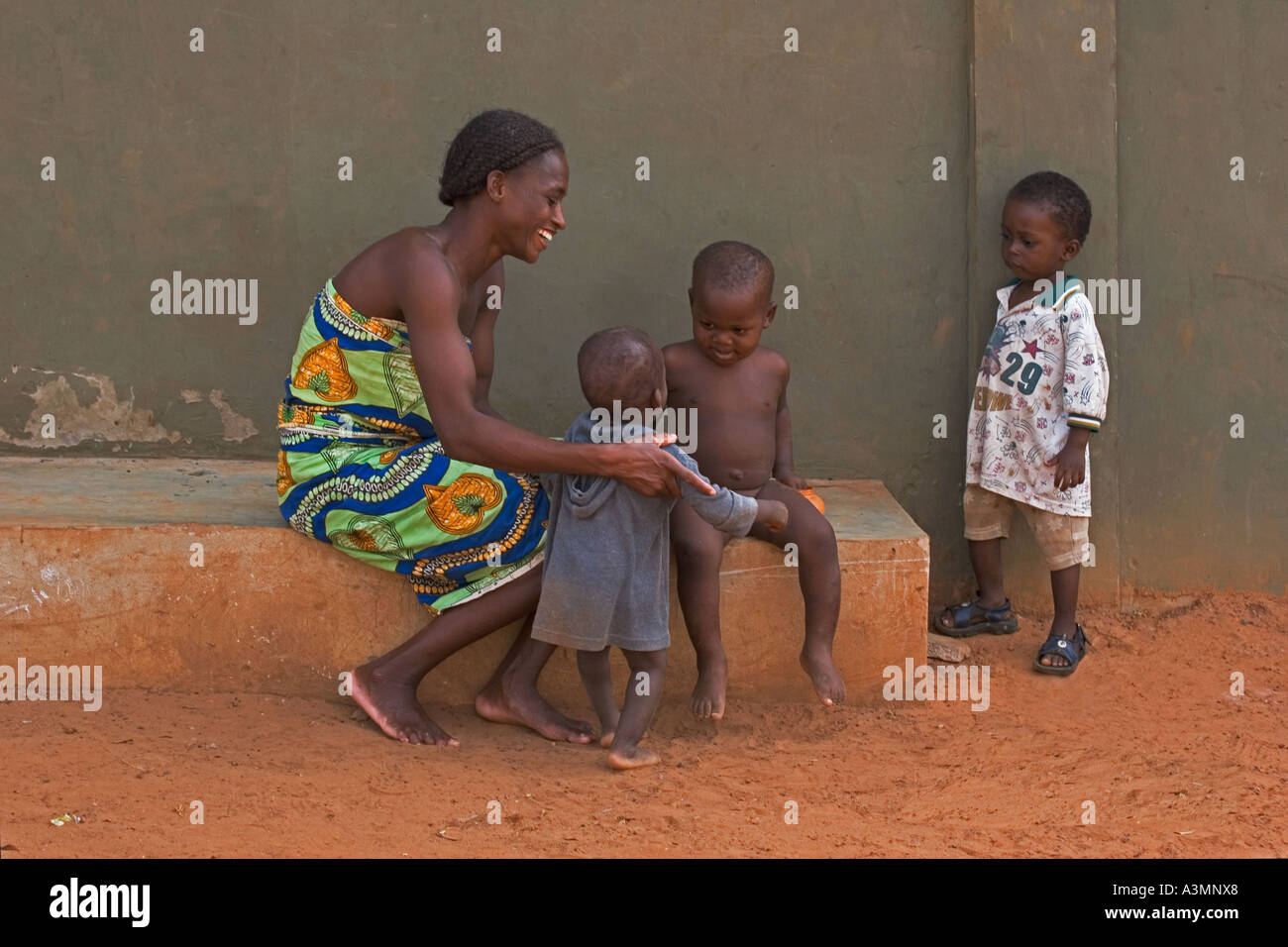 Happy African mother and baby toddler from Ghana with slightly older brother and another brother looking on - Stock Image