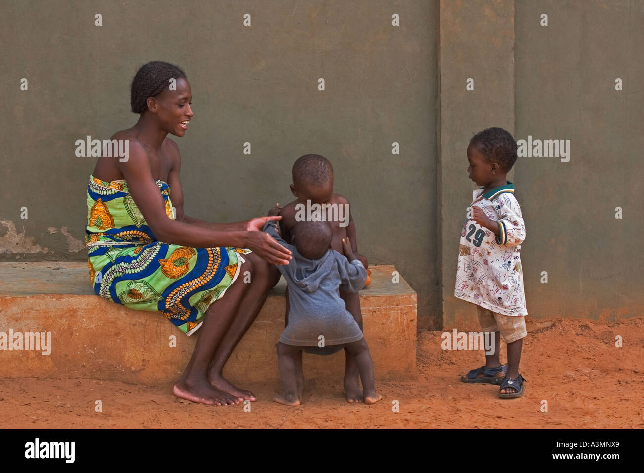 Happy African mother and baby toddler from Ghana hugging slightly older brother with another brother looking on - Stock Image