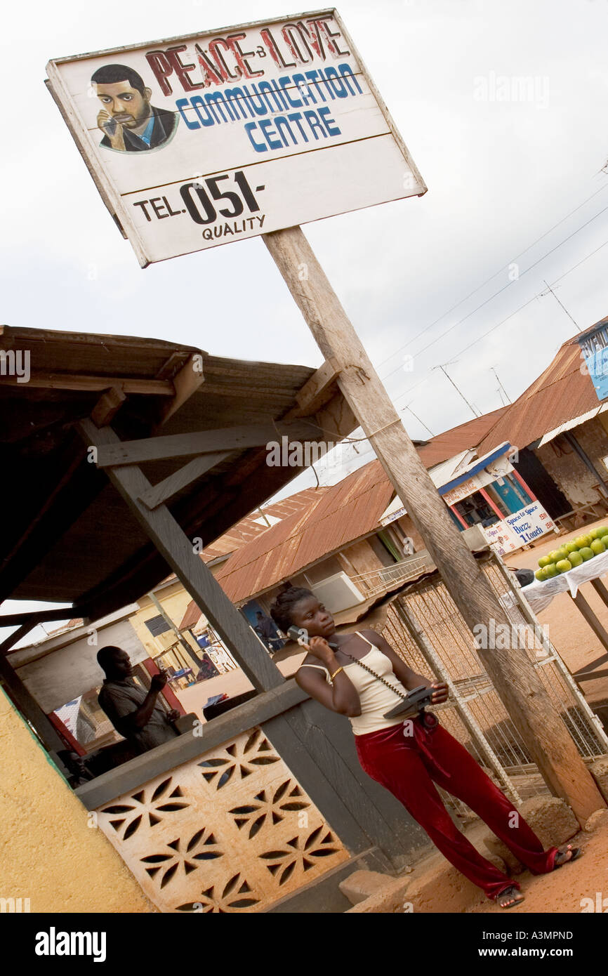 Women stallholder selling phone calls using a conventional handset installed with mobile phone technology, West Africa. - Stock Image