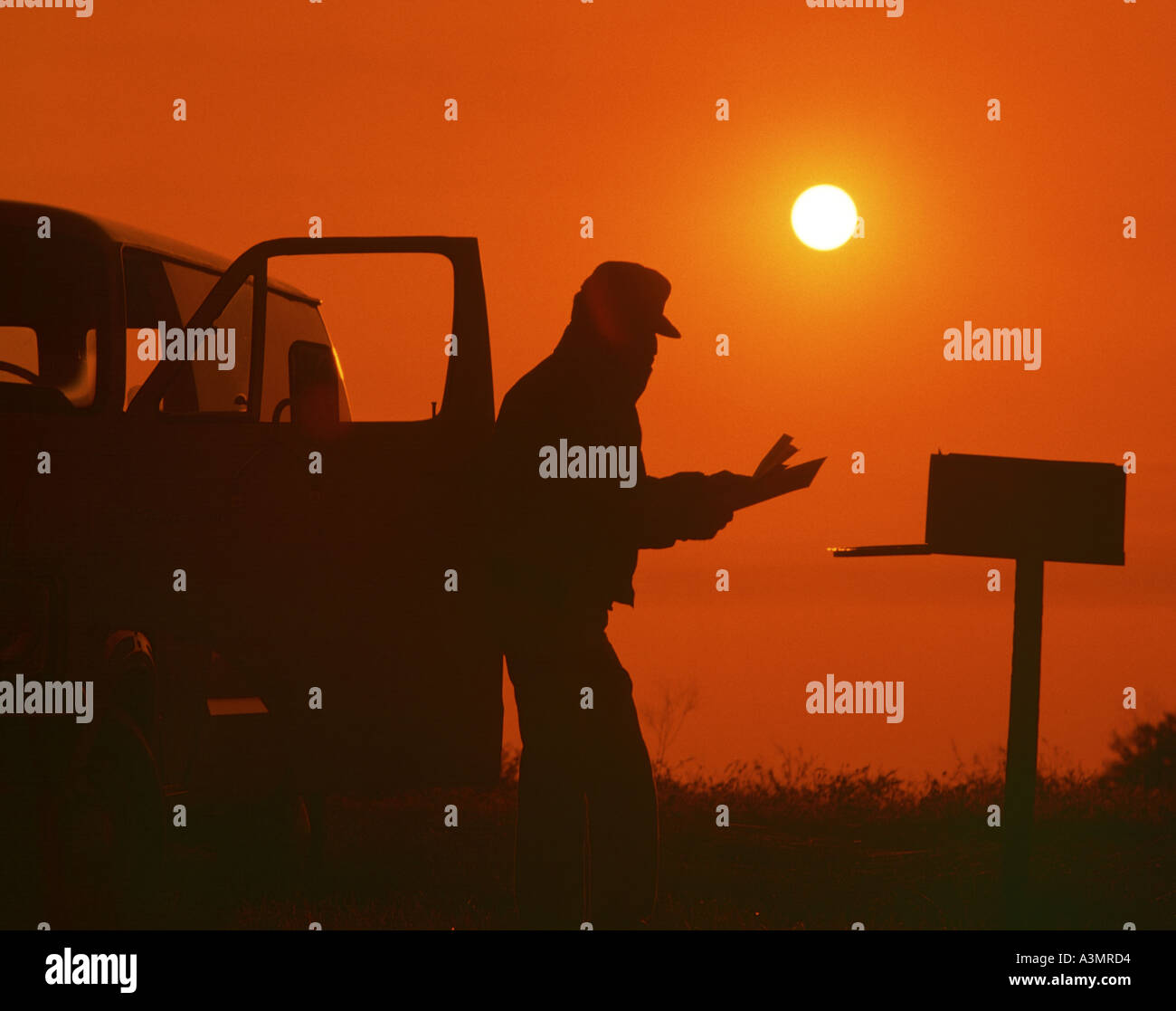 man checking mailbox on farm at sunset - Stock Image