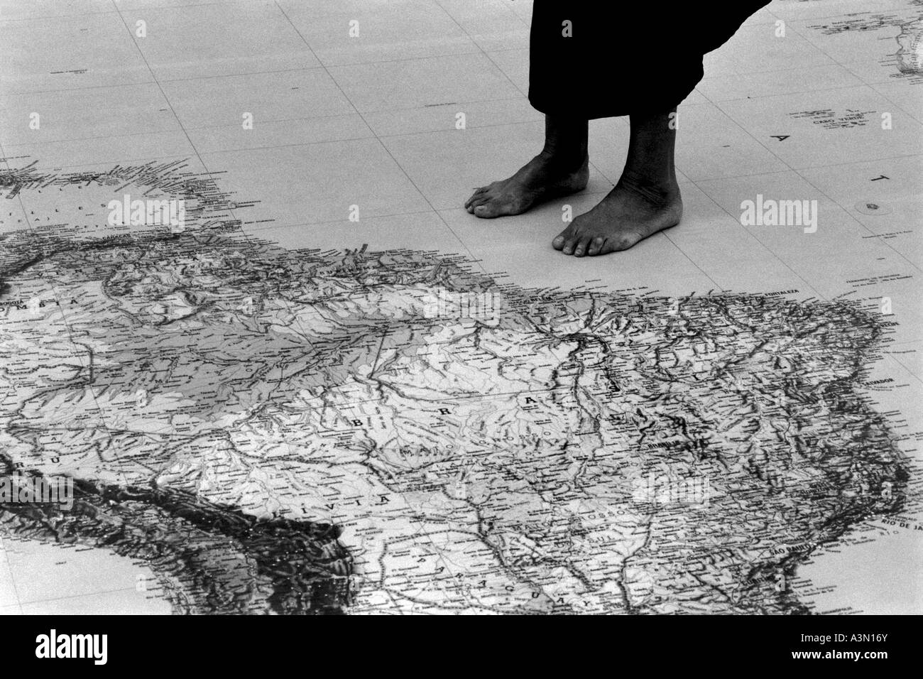 Immigrant standing close to a giant world map Stock Photo