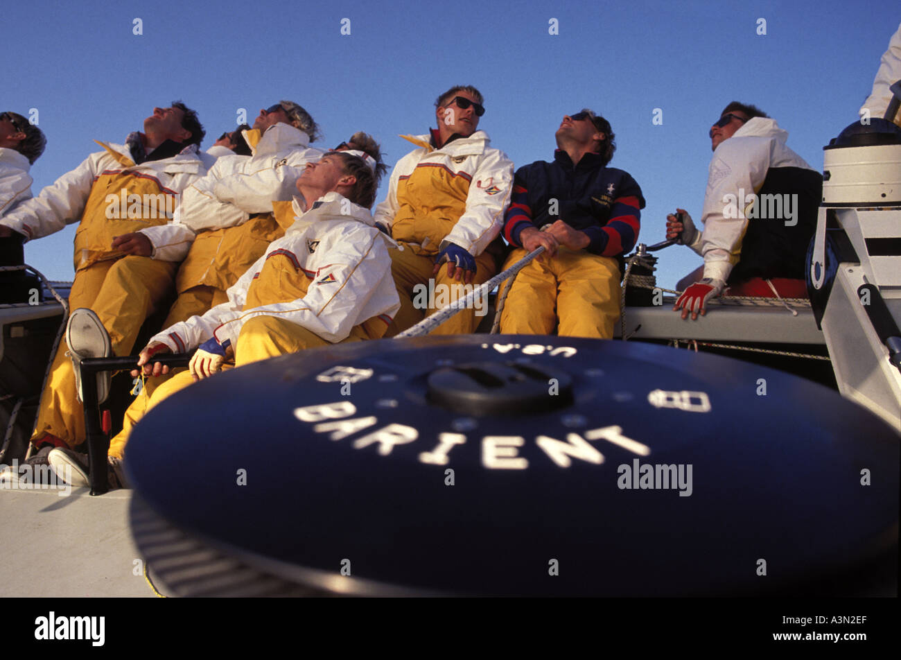The sailing crew line behind a winch on board sail trimming - Stock Image