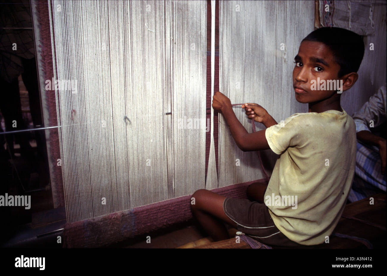 A child works in the carpet factories of Uttar Pradesh India The children are bonded labour trafficked from Bihar and Nepal Their small fingers are adept at manipulating the threads The carpets sell for thousands of dollars in New York and Paris The children who manufacture them are essentially slaves - Stock Image