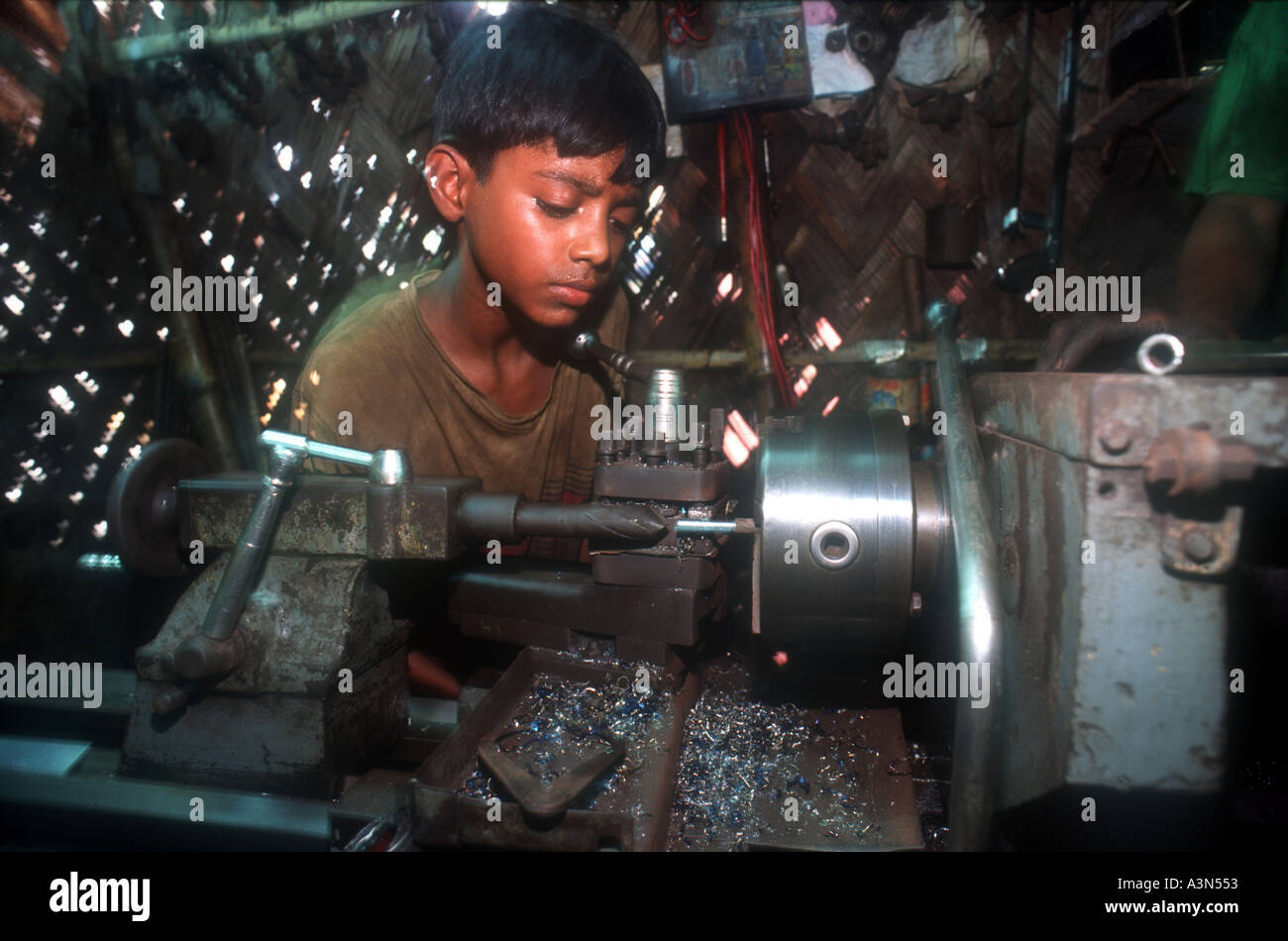 Children work in factories in Dhaka, Banghladesh. They are often run and trafficked by criminal syndicates. - Stock Image