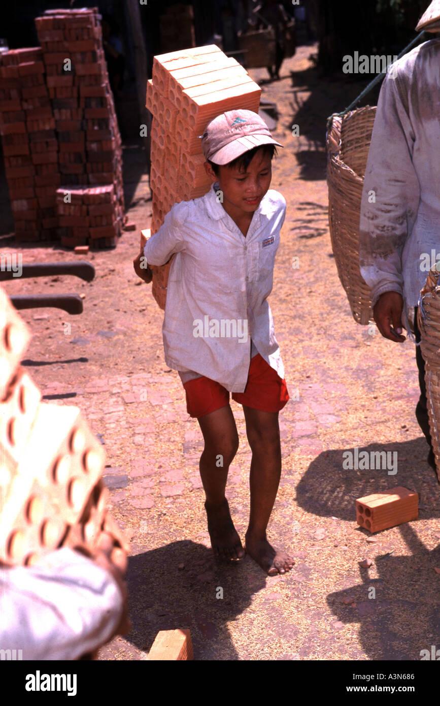 Children work in  brick factories in the Mekong Delta in Vietnam. - Stock Image