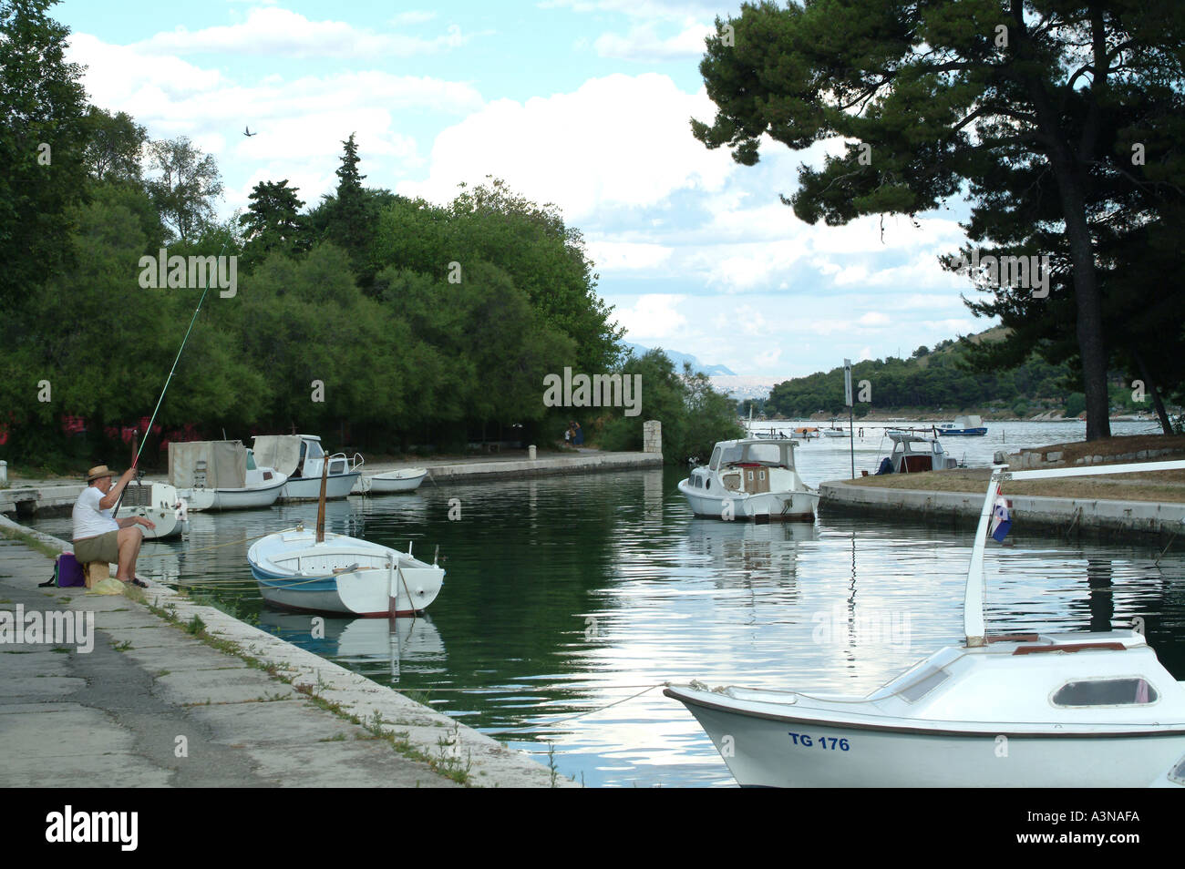 Boats Tied Up with Older Man Fishing in Canal Zone in Trogir Croatia with Mountains in Background - Stock Image
