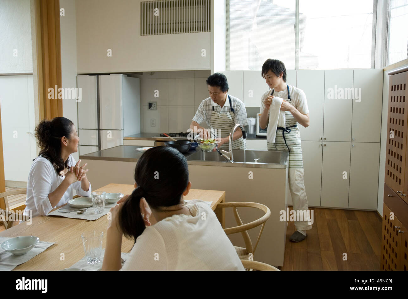 Father and son cooking in kitchen while mother and daughter waiting Stock Photo