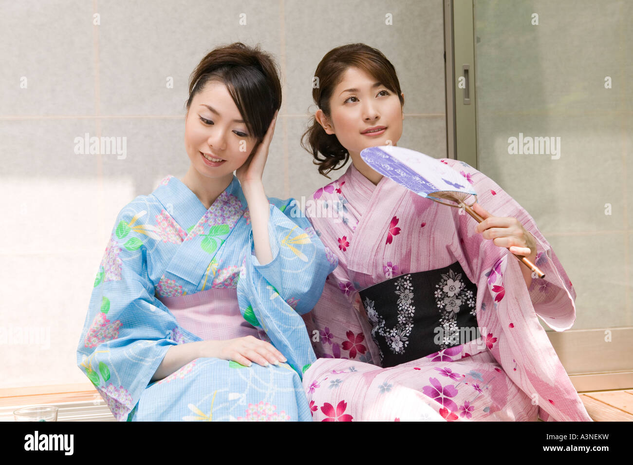 Two young women wearing yukata sitting on porch Stock Photo