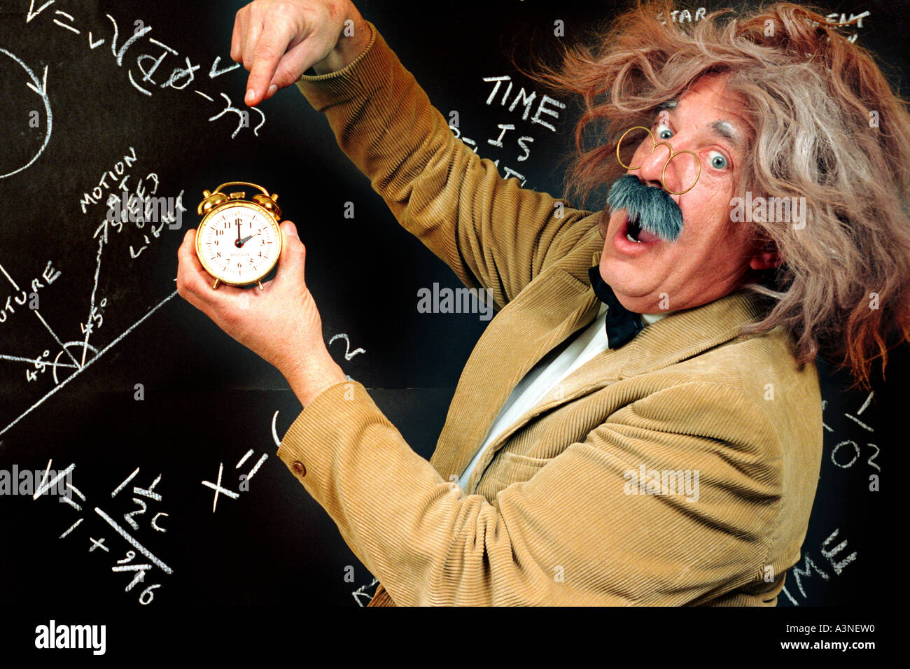 Clock being held by mad professor looking like Einstein with E=MC2 on blackboard with equations about time, time Stock Photo