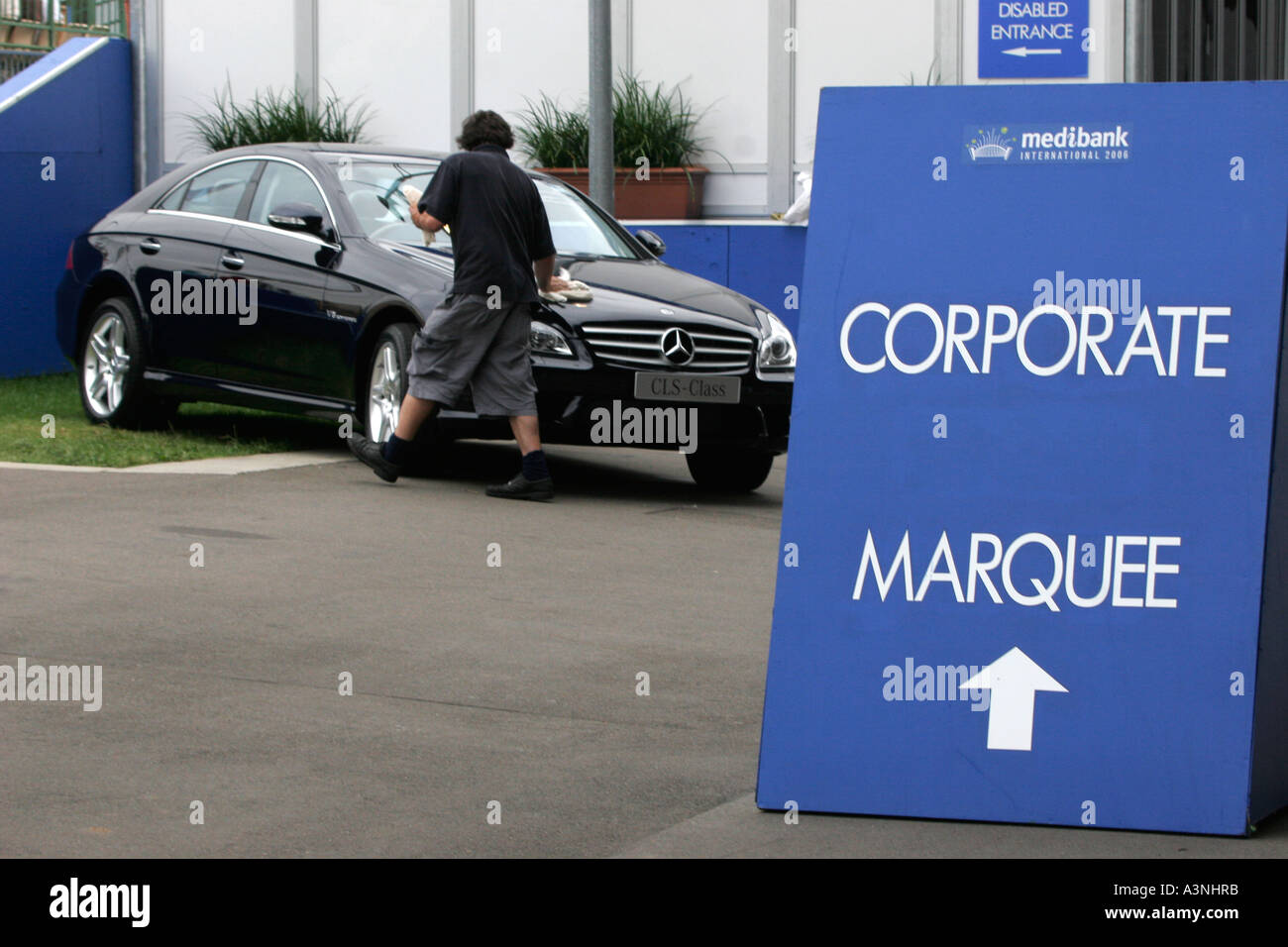A young man polishes the latest model Mercedes Benz at a sports event the the company sponsors - Stock Image