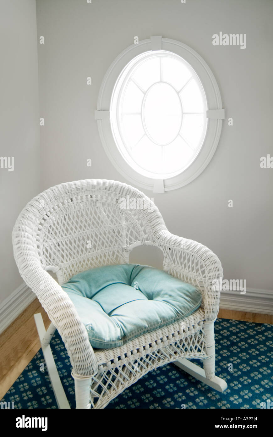 White Rattan Wicker Rocking Chair And Oval Window With Sunshine