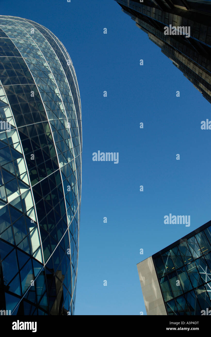 Abstract view of the Gherkin Swiss Re Tower and nearby office buildings shot from directly below London England - Stock Image