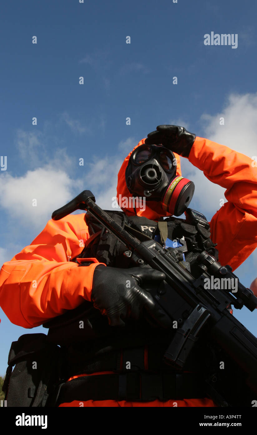A British armed police officer dressed in an anti nuclear chemical warfare suit - Stock Image