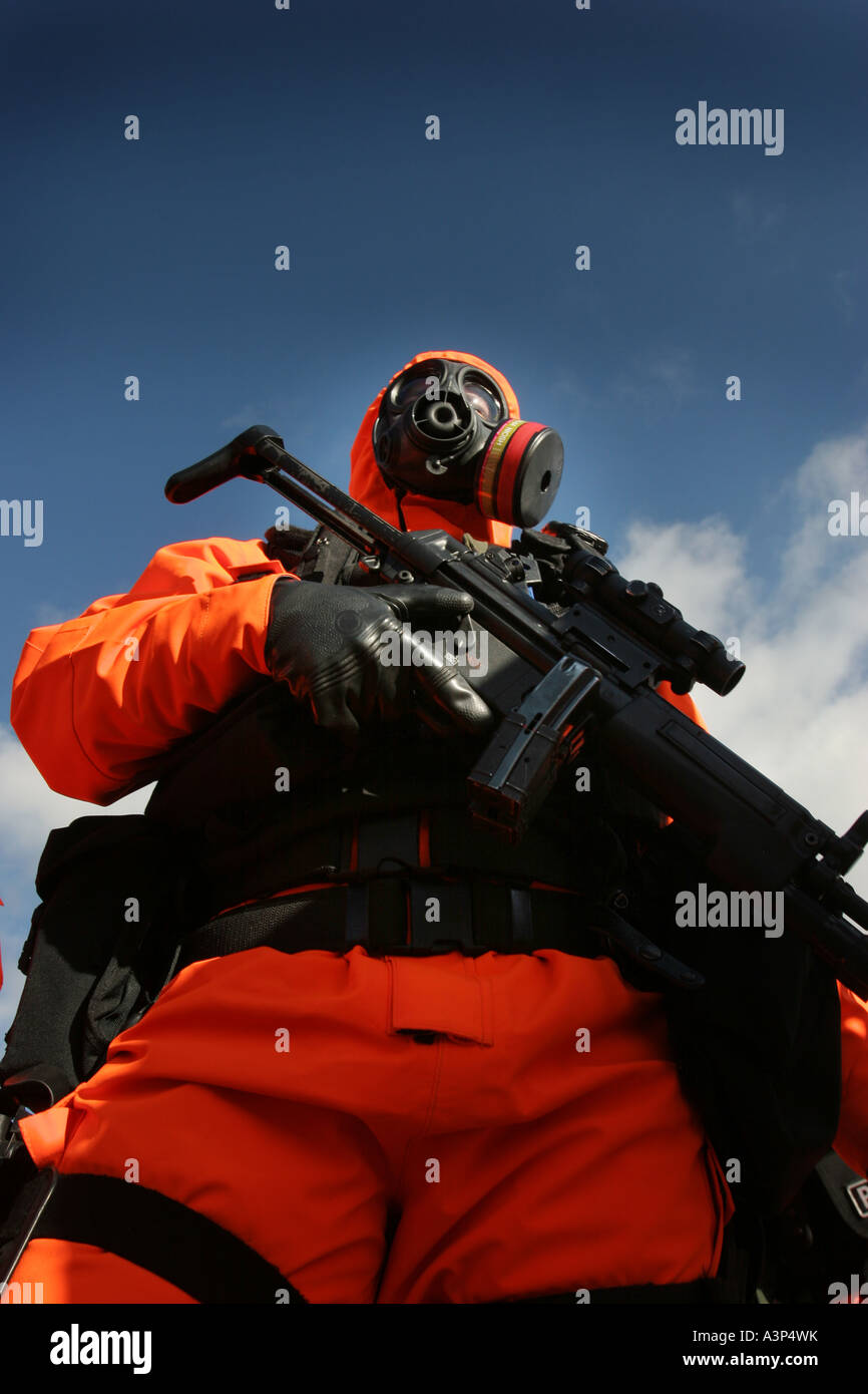 An armed police officer dressed in a chemical nuclear suit in the UK training for terror attacks Stock Photo