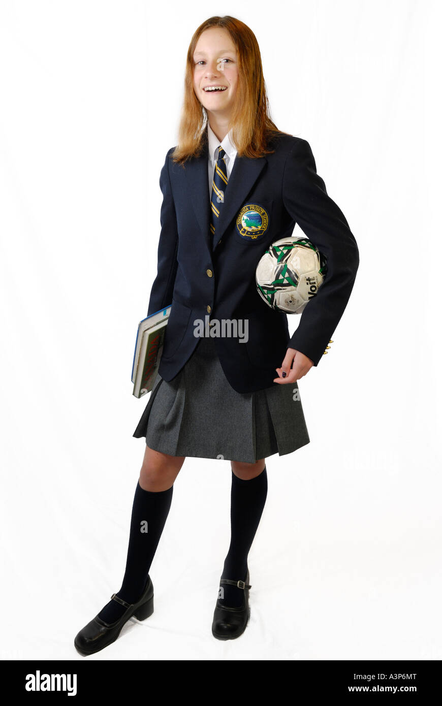 Smiling young girl in private school uniform with books and ball on white background - Stock Image