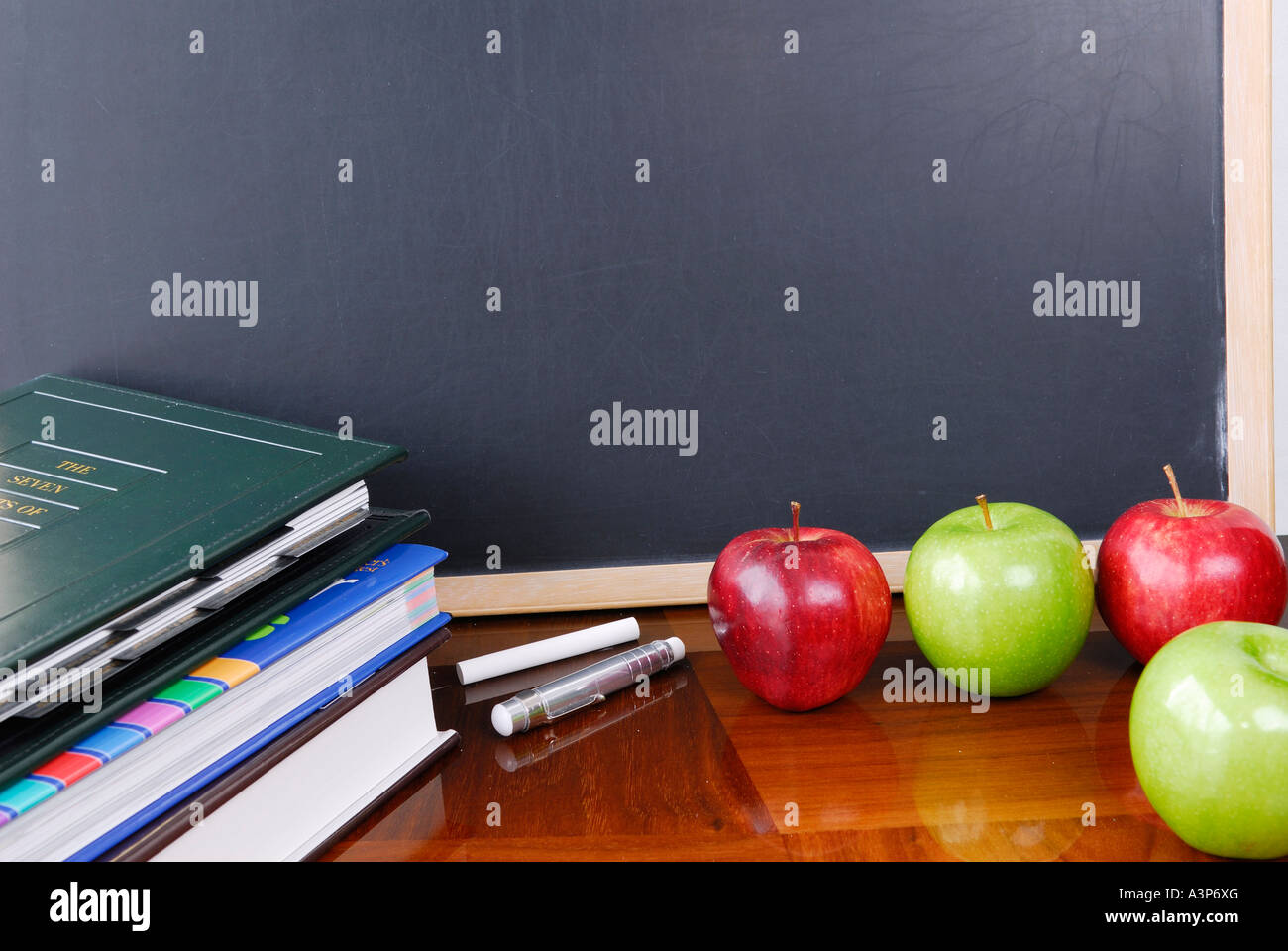 Blank blackboard with school books chalk and apples - Stock Image
