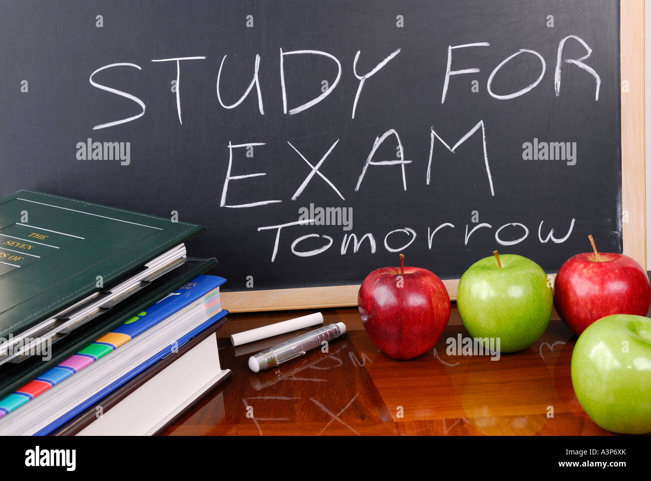 Message on blackboard to study for school exams with books and apples - Stock Image