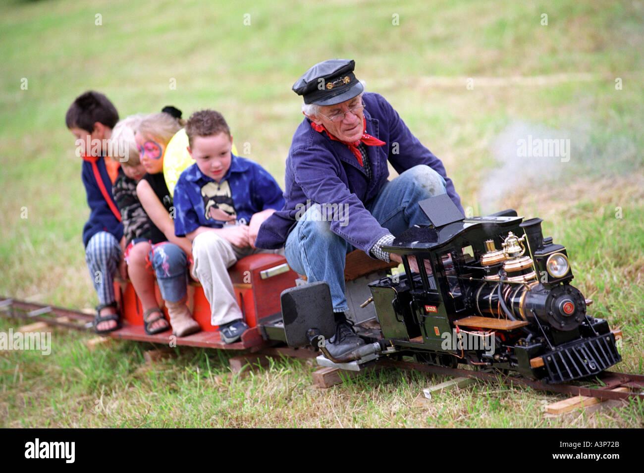 A model steam train taking children for a ride at a village fete in Dorset Britain UK Stock Photo