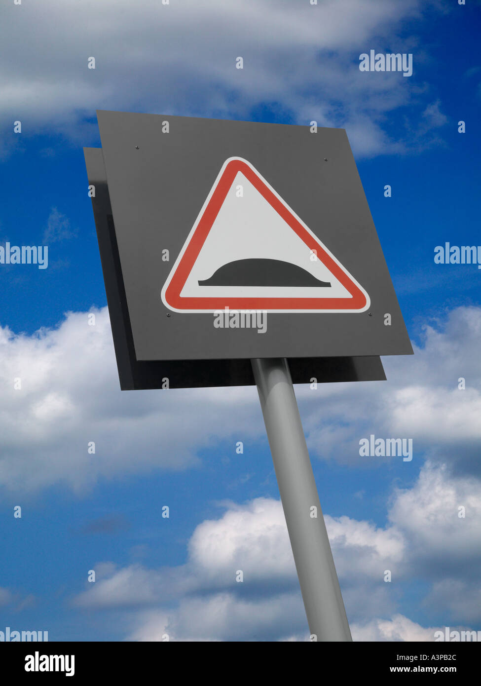 TRIANGULAR RED ROAD TRAFFIC SPEED BUMP SIGN ON GREY BACKGROUND WITH BLUE SKY Stock Photo