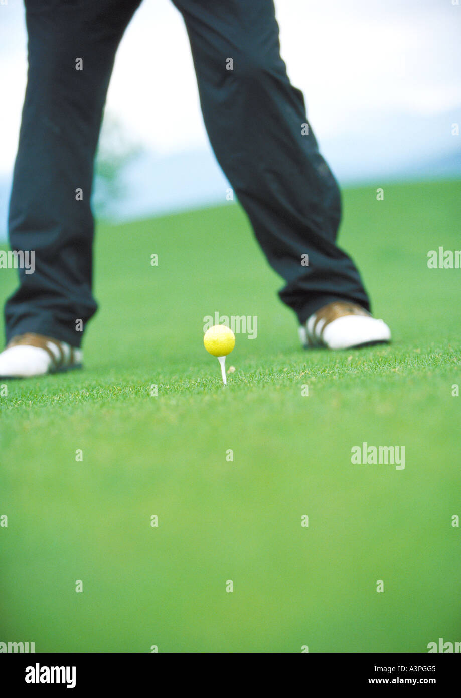 Golfer standing next to teed golf ball - Stock Image
