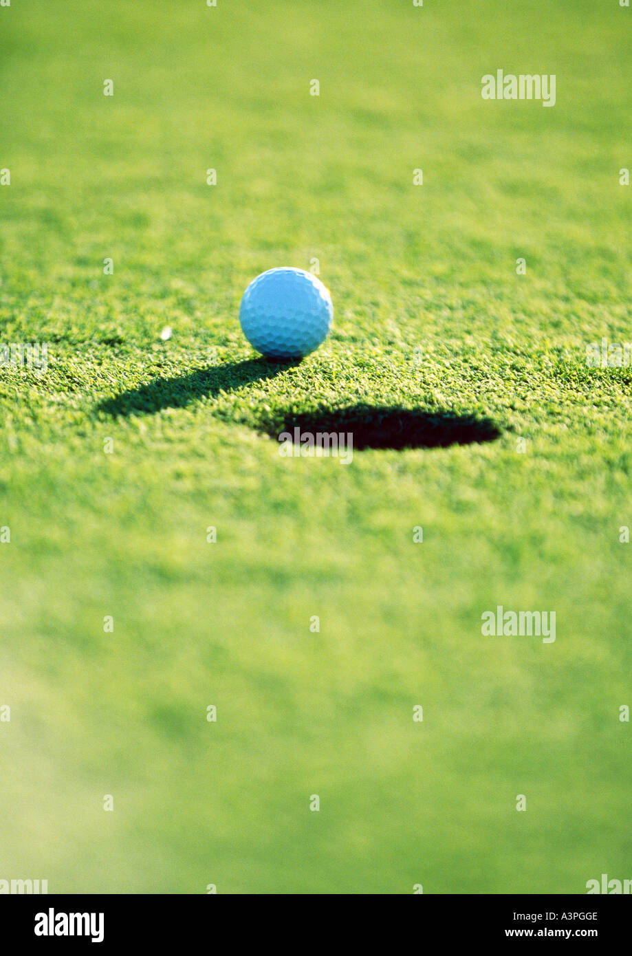Golf ball near hole, close-up - Stock Image