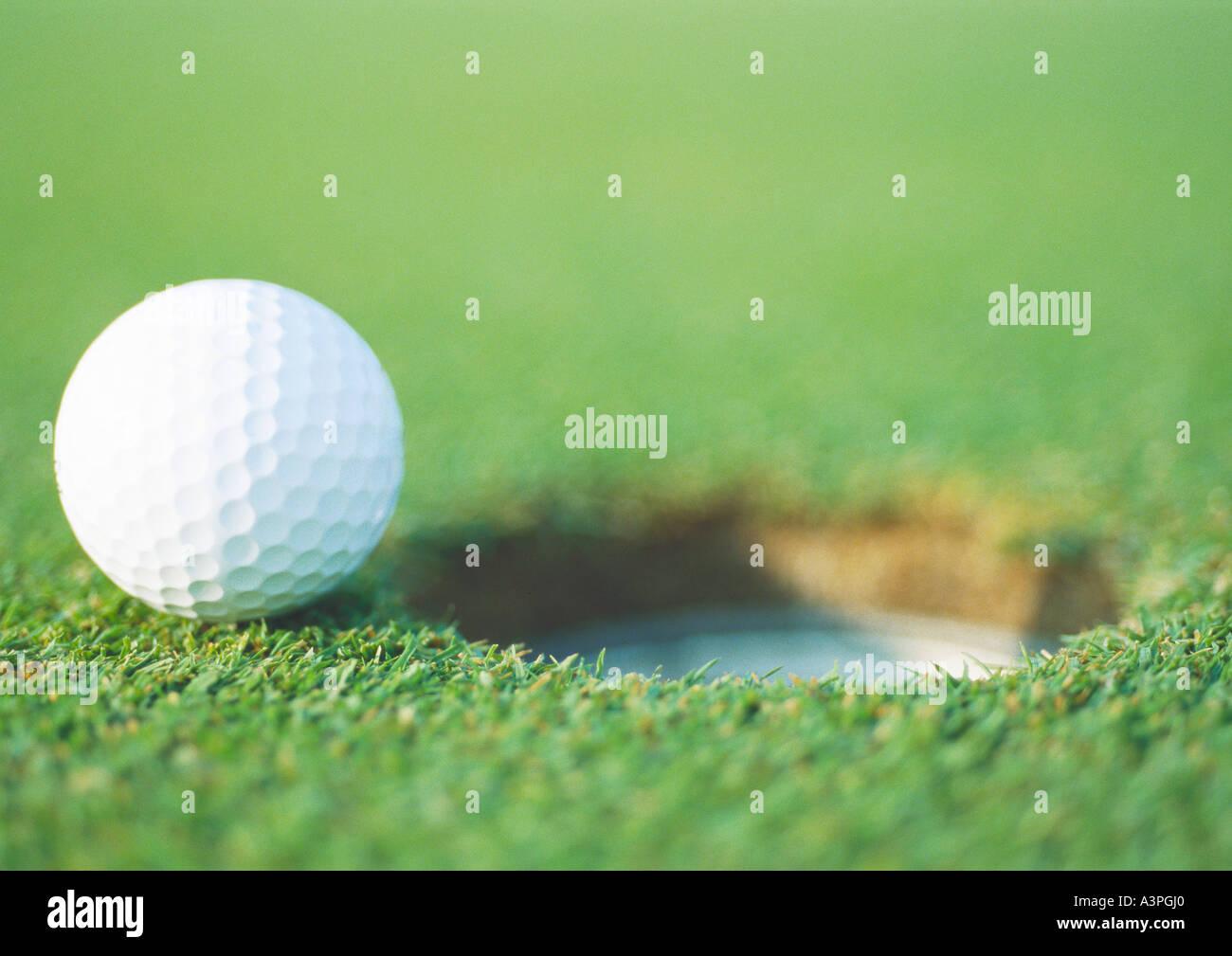 Golf ball at edge of hole, close-up - Stock Image