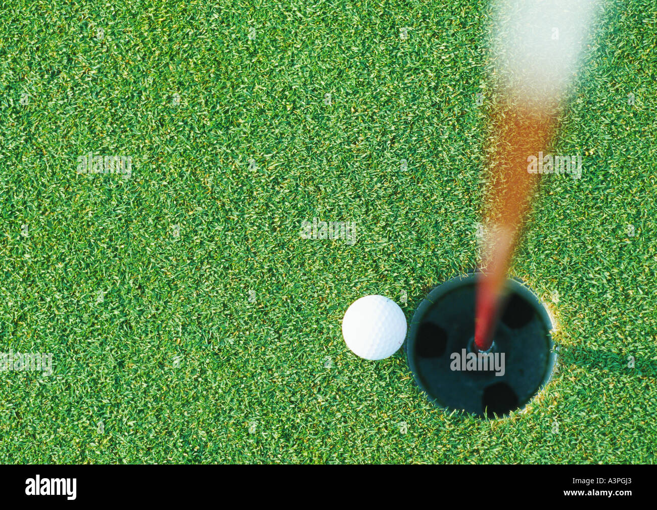Golf ball at edge of hole, view from directly above - Stock Image