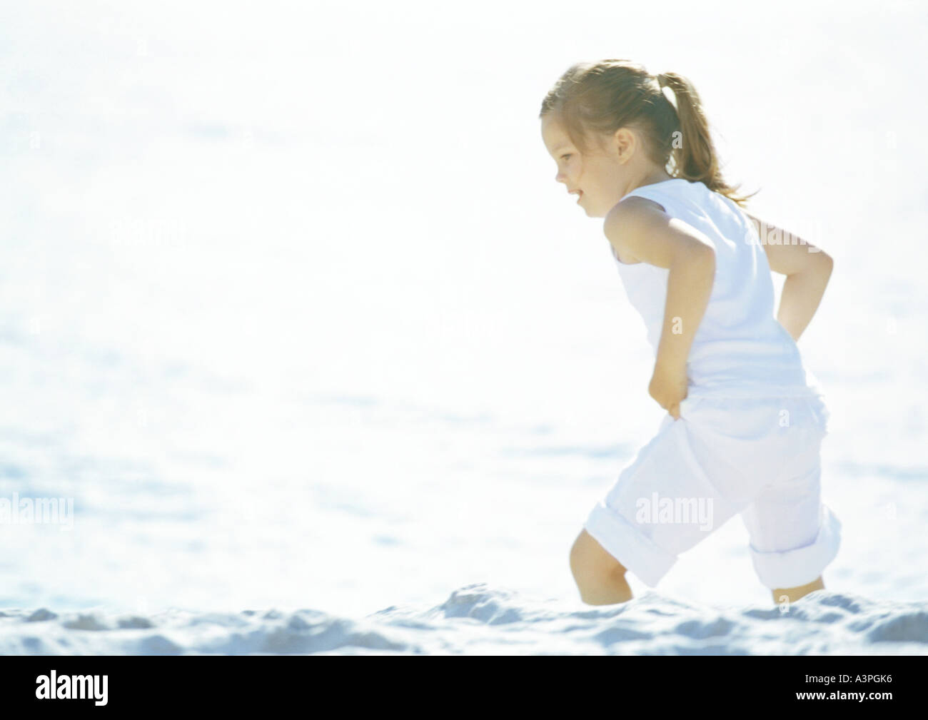 Girl wading in sea with clothes on - Stock Image