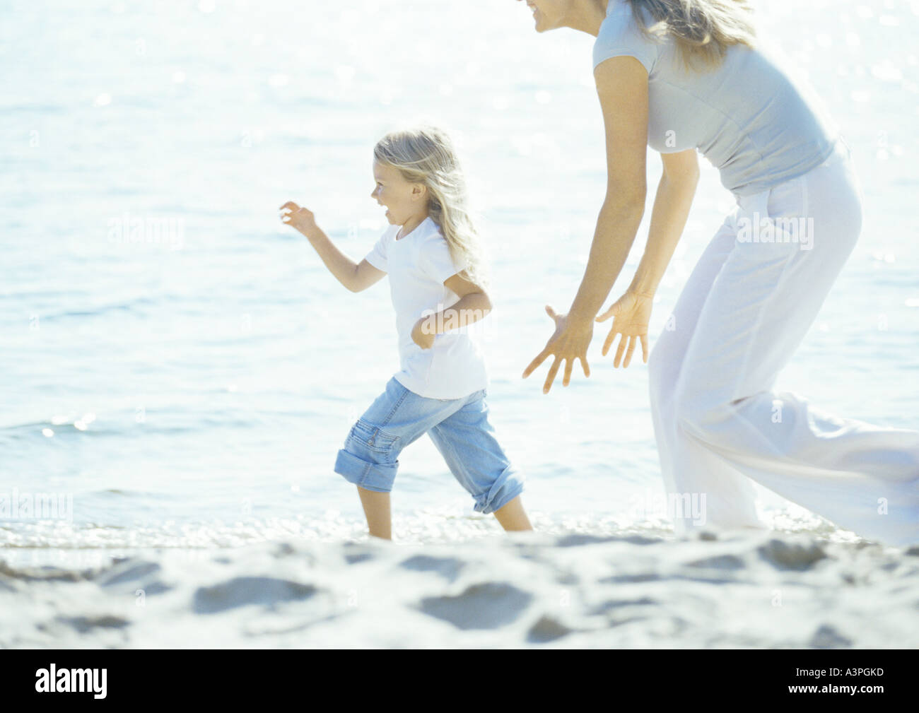 Mother chasing girl on beach - Stock Image