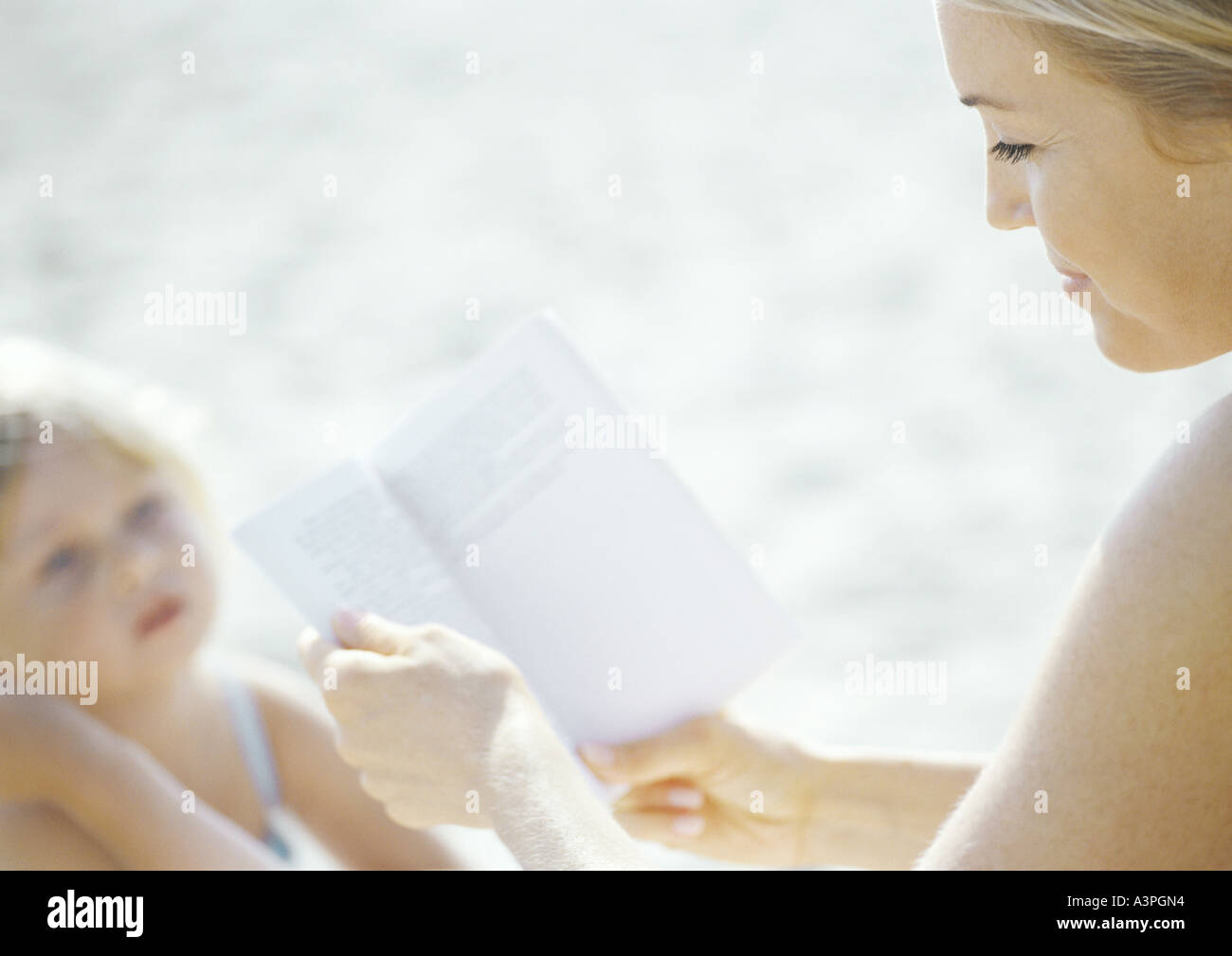 Woman reading book, child looking up at woman - Stock Image