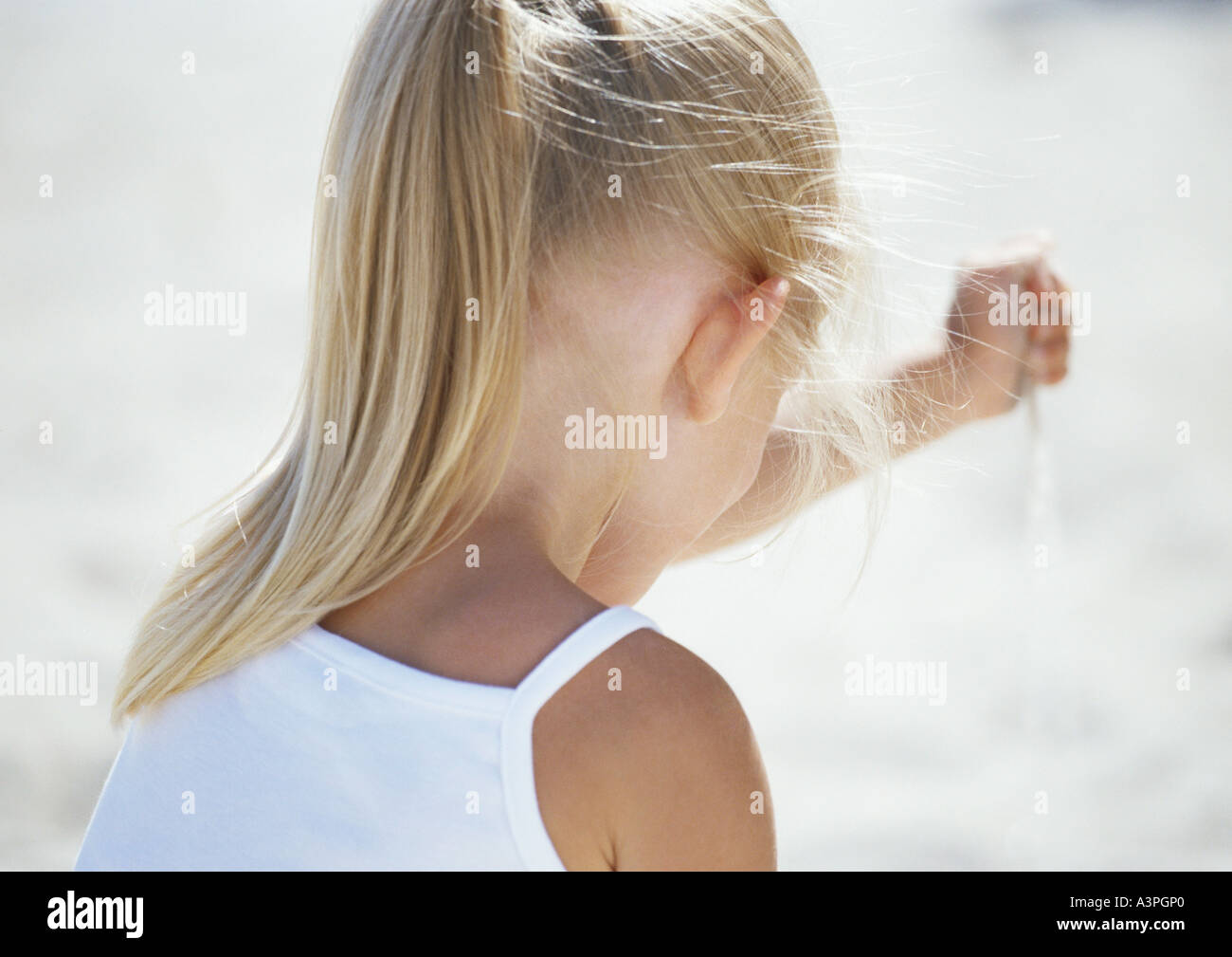 Girl letting sand run through hand, rear view - Stock Image